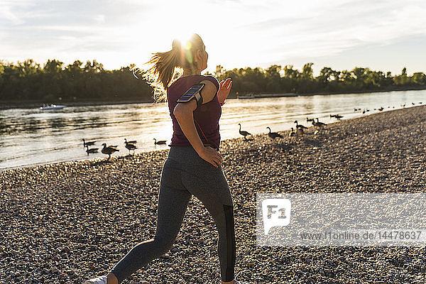 Junge Frau joggt am Fluss
