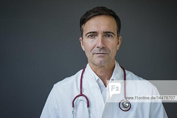 Porträt eines Arztes an einer grauen Wand