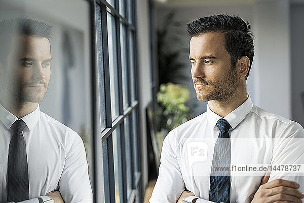 Confident businessman in office looking out of window
