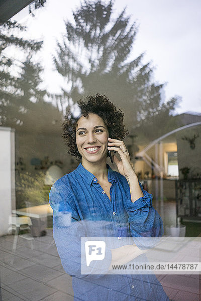 Portrait of smiling woman on cell phone behind window at home