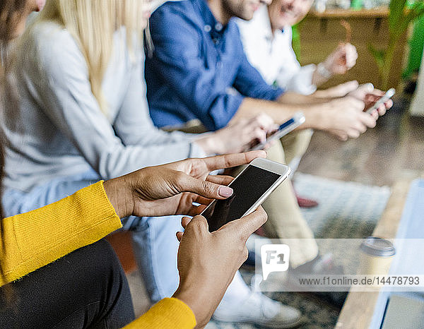 Close-up of business team sitting in loft office using cell phones