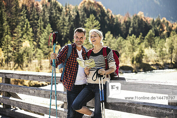 Österreich,  Alpen,  glückliches Paar auf einer Wanderung mit Karte auf einer Brücke