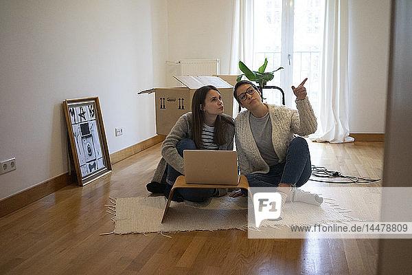 Junge Frauen sitzen auf dem Boden ihrer neuen Wohnung und benutzen einen Laptop