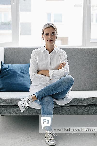 Junge Frau auf Couch sitzend  mit verschränkten Armen