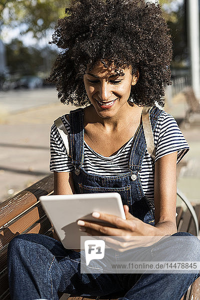 Mid adult woman with curly hair  sitting on a bench  using digital tablet