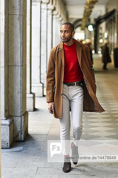 Modischer junger Mann in rotem Pullover und braunem Mantel geht in einer Spielhalle
