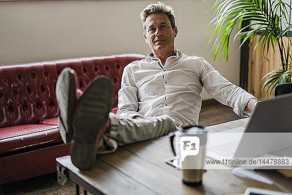 Portrait of businessman sitting with feet on desk