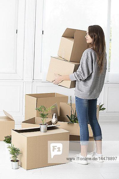 Frau trägt Pappkartons im neuen Zuhause