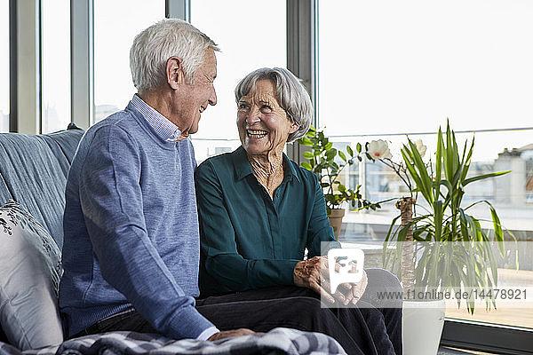 Lachendes Seniorenpaar sitzt zusammen auf der Couch