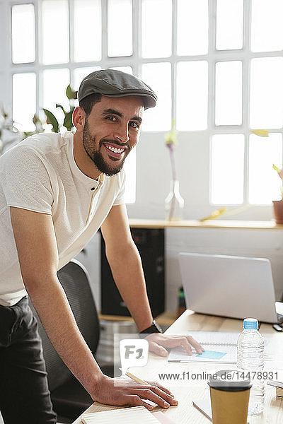 Porträt eines lächelnden jungen Mannes  der sich am Schreibtisch im Büro Notizen macht