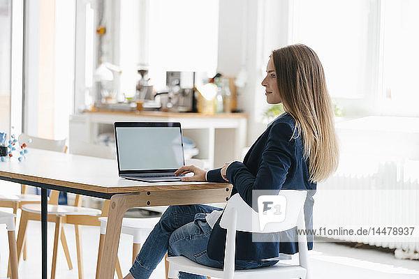 Junge Geschäftsfrau sitzt im Büro und benutzt Laptop