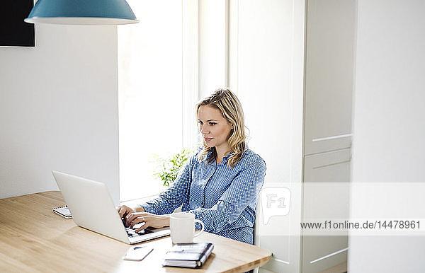 Frau mit Laptop bei der Arbeit zu Hause