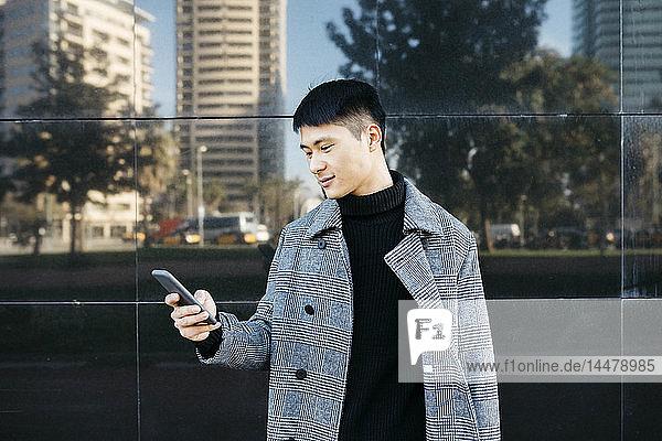Spanien  Barcelona  junger Mann in schwarzem Rollkragenpullover und grauem Mantel beim Blick aufs Handy