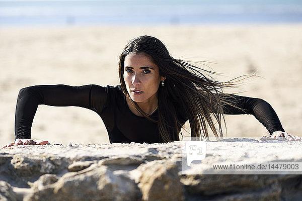 Porträt einer sportlichen Frau beim Training an einer Steinmauer
