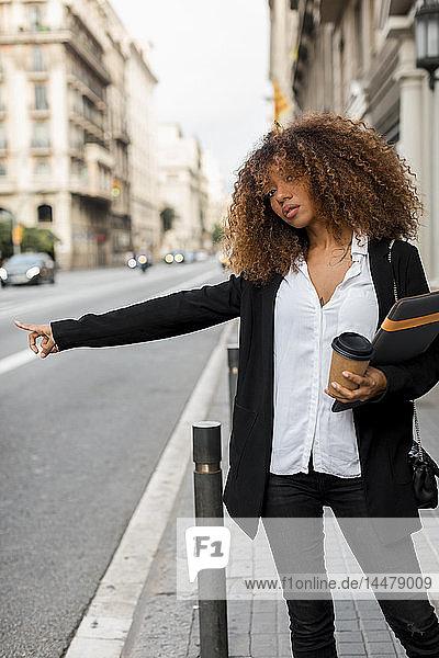 Junge Frau mit Laptoptasche und Kaffee zum Mitnehmen in der Stadt  ein Taxi rufend