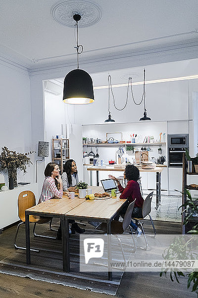Three women with laptop talking at table