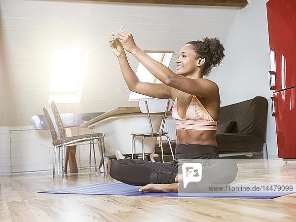 Lächelnde junge Frau  die auf einer Yogamatte sitzt und sich ein Selfie