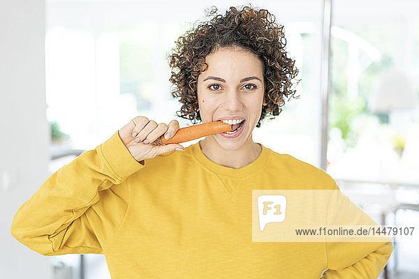Porträt einer Frau  die zu Hause eine Karotte isst