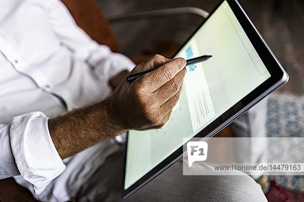 Close-up of businessmen using tablet with digitized pen