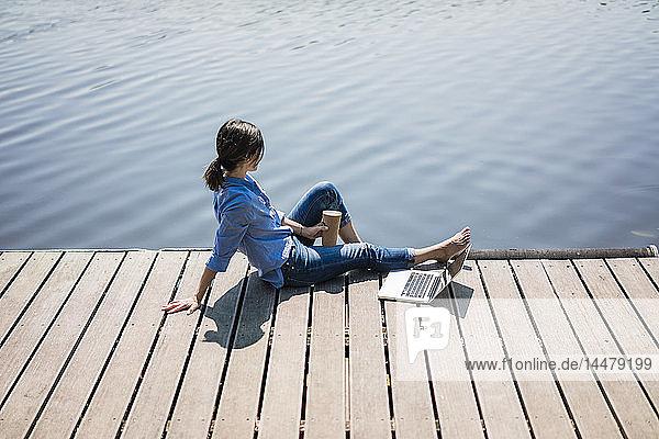 Mature woman sitting on a jetty at a lake  taking a break