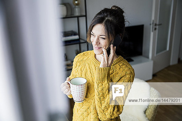 Woman standing at the window  drinking tea  talking on the phone