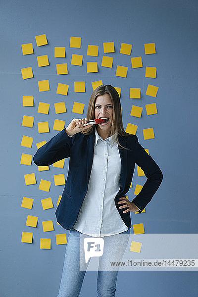 Vor der Wand stehende Yong-Geschäftsfrau  voll gelber Haftnotizen  beißender Filzstift