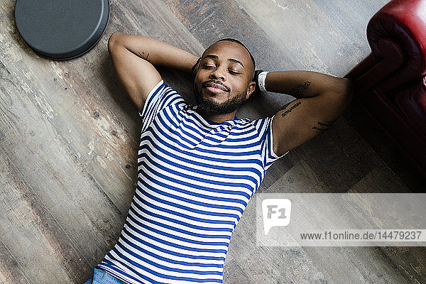 Smiling young man lying on wooden floor with closed eyes