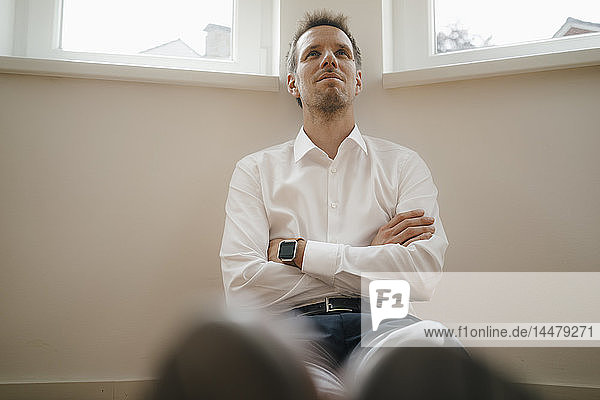 Businessman with smartwatch sitting on ground of his flat  daydreaming
