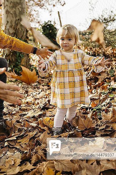 Vater und Tochter genießen im Herbst einen Vormittag im Park und werfen Herbstblätter