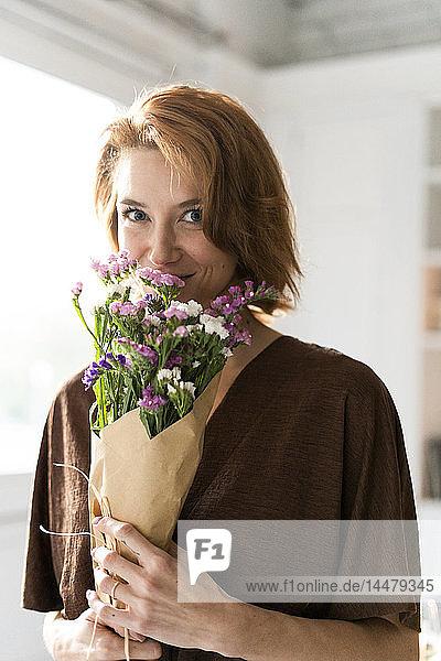 Rothaarige Frau riecht Blumenstrauss