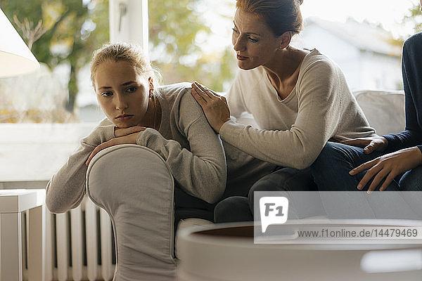 Mutter tröstet trauriges Teenager-Mädchen zu Hause auf der Couch