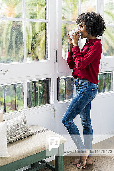 Woman looking out of window at home drinking cup of coffee