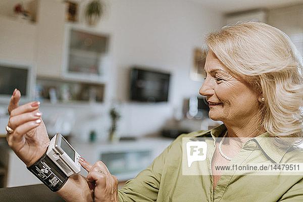 Smiling senior woman taking her blood pressure