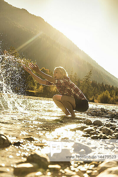 Österreich  Alpen  glückliche Frau auf Wanderung  die an einem Bach mit Wasser spritzt