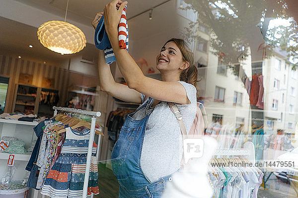 Lächelnde schwangere Frau kauft Babykleidung in einer Boutique