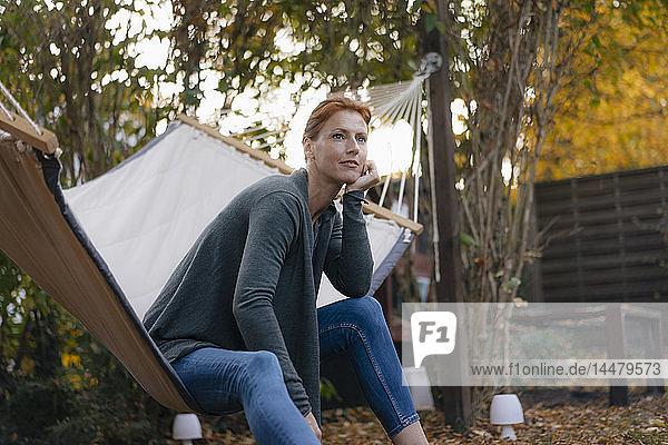 Frau sitzt im Herbst in Hängematte im Garten