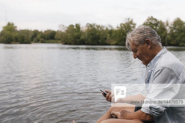 Älterer Mann sitzt mit seinem Handy an einem See