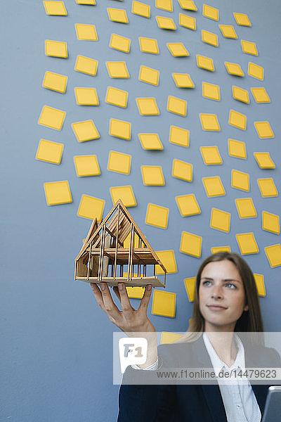 Junge Geschäftsfrau hält Architekturmodell mit gelben Haftnotizen an der Wand hinter Ger