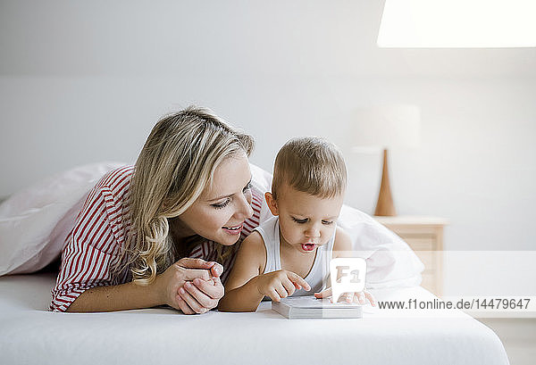 Smiling mother and toddler son lying in bed at home reading a book