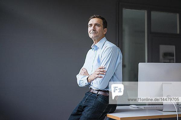 Selbstbewusster Geschäftsmann lehnt sich im Büro an Schreibtisch