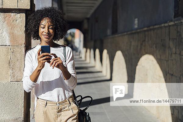 Junge Gelegenheits-Geschäftsfrau benutzt Smartpone in der Stadt