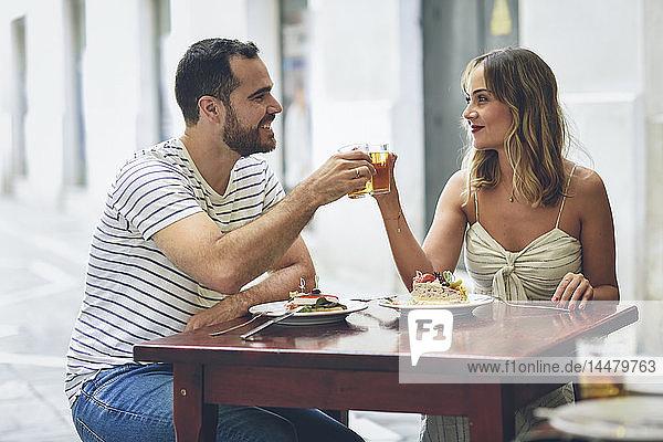 Lächelndes Paar klimpert Bier in einem Restaurant auf der Strasse
