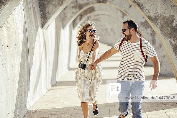 Spanien  Andalusien  Malaga  sorgloses Touristenpaar läuft unter einem Torbogen in der Stadt
