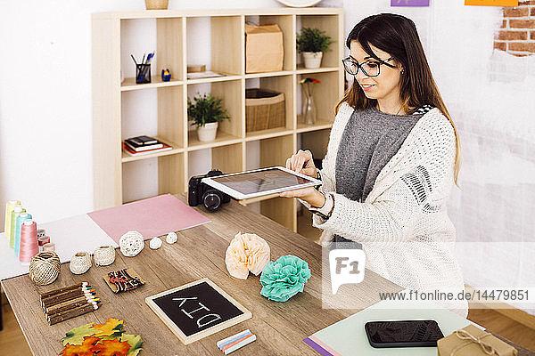 Junge Frau macht Fotos mit dem Tablett für ihren Blog über Blumen aus handgeschöpftem Papier