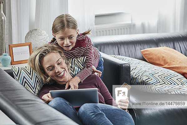 Happy mother and daughter shopping online on couch at home