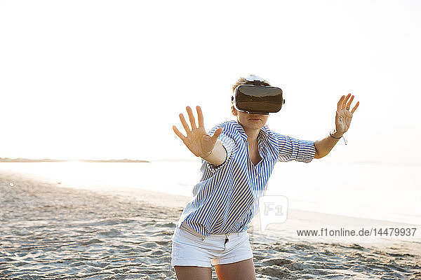 Thailand  Frau mit Virtual-Reality-Brille am Strand im Morgenlicht