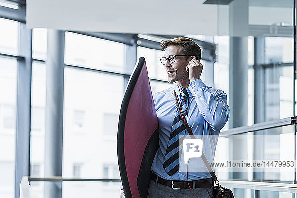 Businessman with earphones carrying surfboard in office