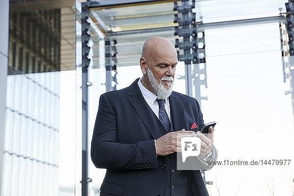 Eleganter Geschäftsmann mit Smartphone in der Stadt