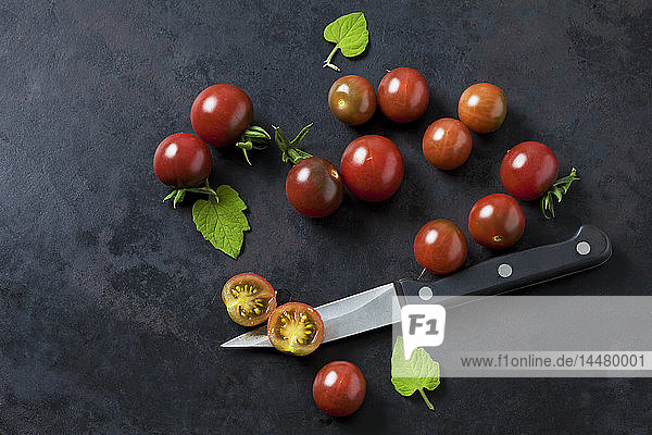 Ganze und in Scheiben geschnittene rispische Tomaten 'Black Cherry'  Blätter und Küchenmesser auf dunklem Grund