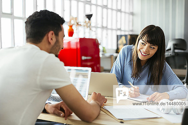 Lächelnde Kollegen am Schreibtisch im Büro
